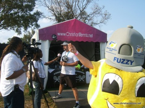 Beach Tennis mascot getting a pic while Scott Paschal gives interview